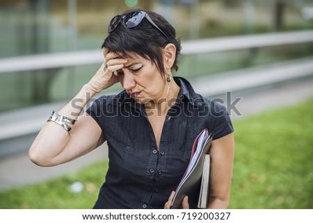 Mature business woman having a headache, returning home from work #719200327