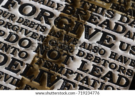 Word of the Lord's Prayer on the old  black weathered wooden plank background. Close-up. #719234776