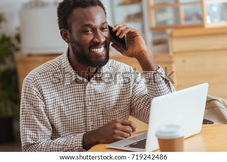Cheerful man talking on phone while working in cafe #719242486