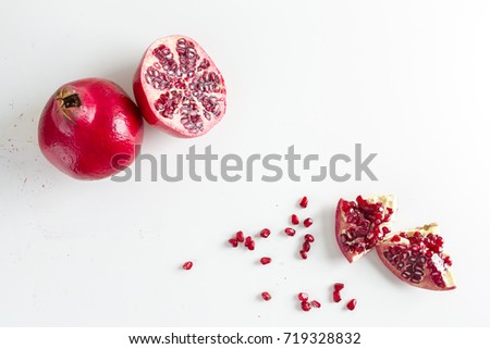 ISOLATED POMEGRANATE WITH HALF PIECE AND SEED ON WHITE BACKGROUND
