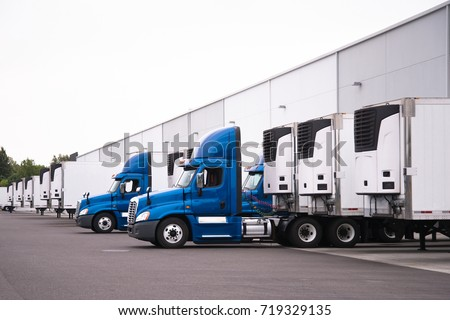 A day cab big rigs semi trucks with a reefer trailers stand near the gate of the warehouse next to other reefer trailers that are loaded and unloaded to deliver perishable and frozen food to consumers #719329135