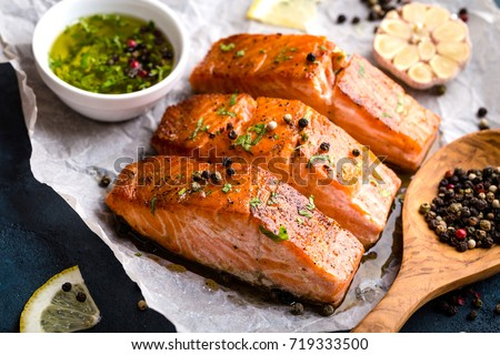 Delicious fried salmon fillet, seasonings on blue rustic concrete table. Cooked salmon steak with pepper, herbs, lemon, garlic, olive oil, spoon. Grilled fresh fish. Fish for healthy dinner. Close-up #719333500