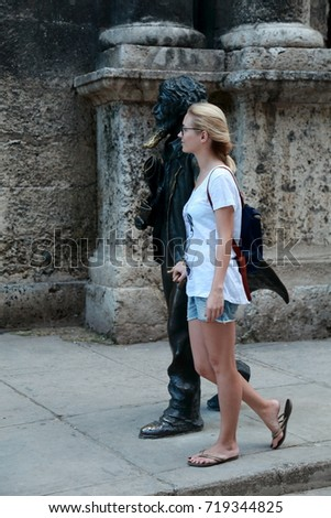 Pretty blond female tourist in shorts and shirt holding hands with male bronze statue, Havana, Cuba, December 11, 2013 #719344825