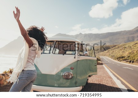 Woman on roadtrip standing outdoors on countryside road near a mini van. Female having fun on vacation. Royalty-Free Stock Photo #719354995