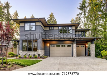 New construction home exterior with contemporary house plan  features gray wood siding, stone columns and two garage spaces. Northwest, USA Royalty-Free Stock Photo #719378770