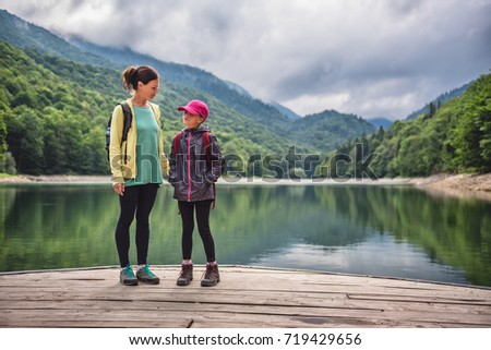Mother and daughter standing on the pier by the mountain lake #719429656