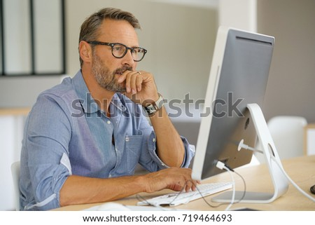 Businessman working on desktop computer #719464693