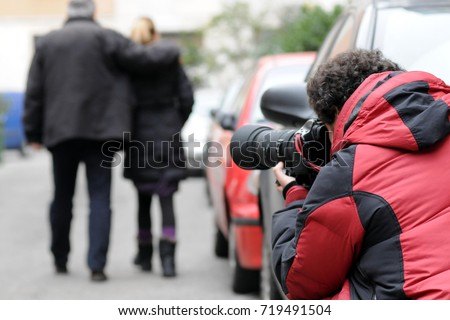 Paparazzo - Paparazzi - man taking pictures scoop - private investigator photographs and takes a couple on the street #719491504