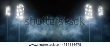 stadium lights and smoke against dark night sky background Royalty-Free Stock Photo #719586478