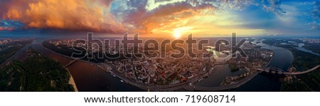 A big panorama of the city of Kiev on Podol at sunset. A modern metropolis in the center of Europe against the backdrop of a dramatic orange sky from a bird's eye view. Aerial view Royalty-Free Stock Photo #719608714