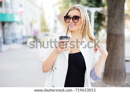 woman with take away cup of coffee or tea walking along the street. #719653015