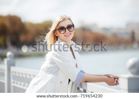 A beautiful young girl is walking along the embankment #719654230