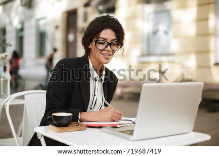 Portrait of African American girl sitting at the table of cafe and writing in her notebook while looking in laptop. Beautiful lady with dark curly hair in jacket working with cup of coffee on table #719687419