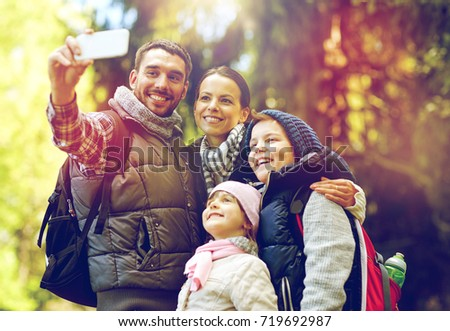 travel, tourism, hike and technology concept - happy family with backpacks taking selfie by smartphone in woods