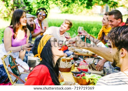 Happy friends making a picnic in the garden outdoor - Young trendy people having fun eating and drinking while sitting on the grass in the nature - Youth, friendship, food concept - Focus on female