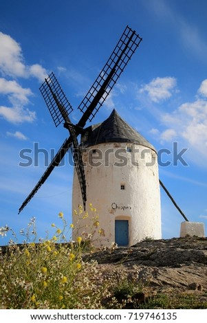 Isolated windmill stands quietly on the hill and enjoys sunbath of a good weather day, Consuegra, Central Spain #719746135