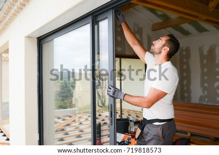 handsome young man installing bay window in a new house construction site Royalty-Free Stock Photo #719818573
