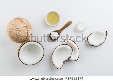 Homemade coconut products on white wooden table background. Oil, scrub, milk and lotion from top view. Good for space and background. #719852194
