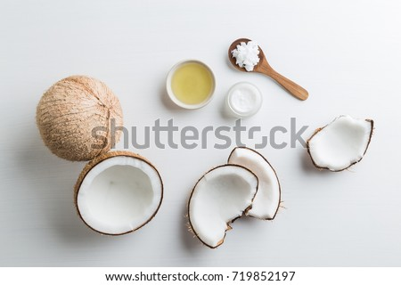 Homemade coconut products on white wooden table background. Oil, scrub, milk and lotion from top view. Good for space and background. #719852197