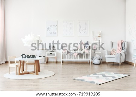 Pink blanket on grey armchair in pastel kid's room with small table and plush toy on white cabinet