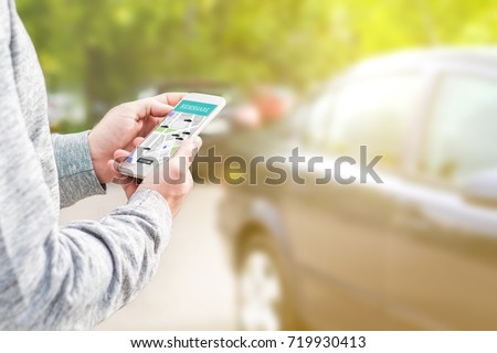 Online ride sharing and carpool mobile application. Rideshare taxi app on smartphone screen. Modern people and commuter transportation service. Man holding phone with a car in background. Royalty-Free Stock Photo #719930413