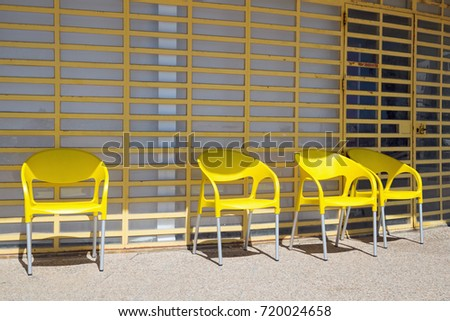 Bright yellow chairs lined up against a bright yellow window shutter. #720024658