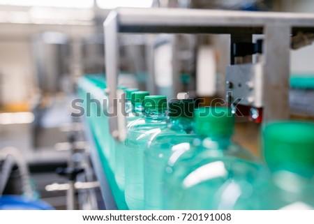 Bottling plant - Water bottling line for processing and bottling carbonated water into green bottles. Selective focus.  #720191008