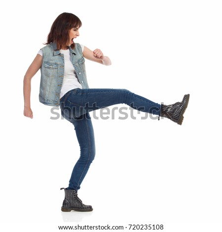 Young woman in jeans vest and black boots is shouting and kicking. Side view. Full length studio shot isolated on white. Royalty-Free Stock Photo #720235108