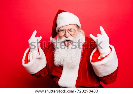 It's party time! Holly jolly swag x mas and noel!  Cool funny playful naughty grandfather with sticking tongue, comic grimace, fooling around isolated on red background, shows rock gesture #720298483