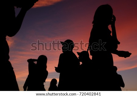 Group of people taking photograph of sunset with smartphone.  #720402841