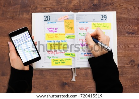 High Angle View Of A Businessperson With Mobile Phone Writing Schedule In Diary #720415519