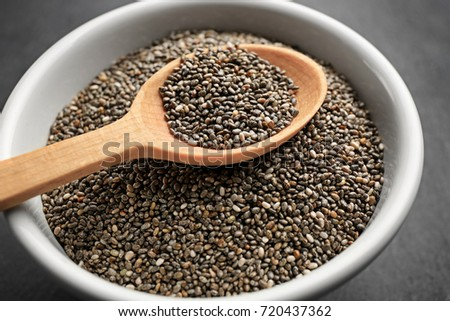 Chia seeds in wooden spoon over bowl, closeup #720437362