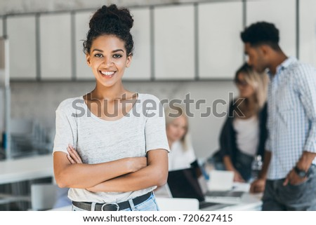 Enthusiastic female african student enjoying company with friends in lecture hall. Indoor portrait of smiling black office worker posing with arms crossed in front of foreign colleagues. Royalty-Free Stock Photo #720627415