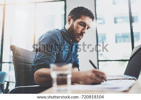 Young pensive man working at sunny loft office on laptop.Businessman making notes on paper documents reports.Blurred background.Horizontal #720818104
