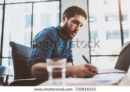 Young attractive man working at sunny loft office on laptop while sitting at wooden table.Businessman analyze digital reports on notebook computer.Blurred background,horizontal #720818332