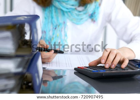 Female bookkeeper or financial inspector  making report, calculating or checking balance. Internal Revenue Service checking financial document. Audit concept #720907495