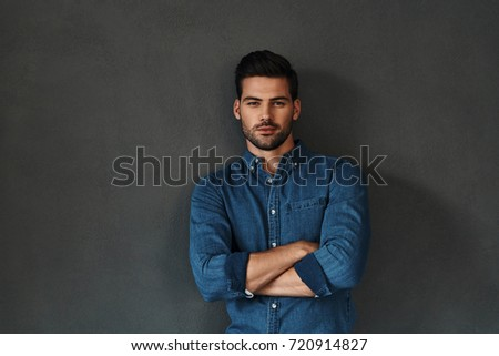 Confidence and charisma. Good looking young man keeping arms crossed and looking at camera while standing against grey background #720914827