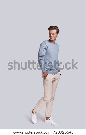 Confidence and charisma. Full length of handsome young man looking away with smile and keeping hands in pockets while standing against grey background #720925645
