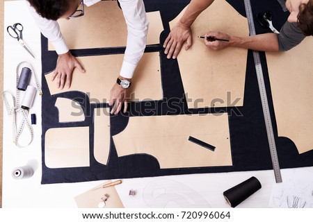 High angle view of concentrated young tailors using sewing patterns while working on creation of custom-made male jacket #720996064