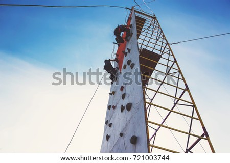 Young boy climbing up an artificial rock wall. Two young athlete's compete in climbing a vertical climbing wall on the blue sky background. #721003744