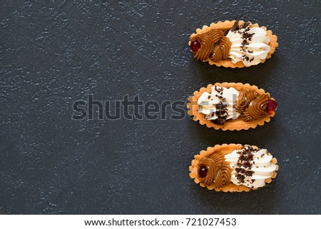 Cream cakes on a dark background. Top view, copy space #721027453