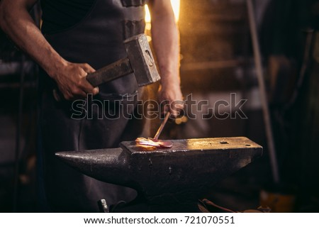 Close-up of blacksmith manually forging the molten metal on the anvil in smithy workshop. Blacksmith working metal with hammer in the forge #721070551
