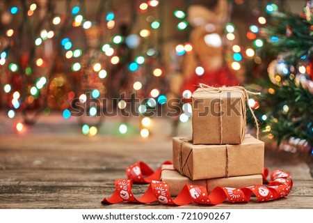 Gift boxes with a large red bow  against a background bokeh of twinkling party lights. Luxury New Year gift. Christmas gift. Christmas background with gift box. Christmastime celebration #721090267