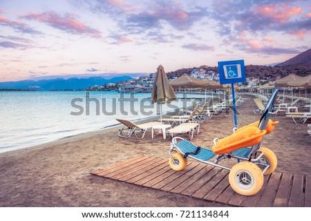 Beach wheel chair for disabled swimmers, Elounda, Crete, Greece.