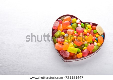 Colored candies, sweets and lollipops. On a white wooden background. Top view. Free space. #721151647