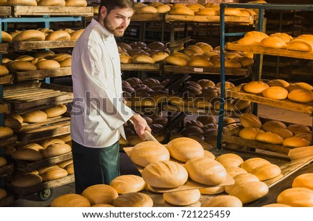 Baker. A young handsome bakery worker on the background of bread, takes bread from a stove with a wooden shovel. Industrial production of bakery products. a man in the baker's special clothing. Bakery #721225459