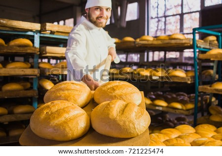 Baker. A young handsome bakery worker on the background of bread, takes bread from a stove with a wooden shovel. Industrial production of bakery products. a man in the baker's special clothing. Bakery #721225474