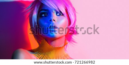 Fashion model woman in colorful bright lights, portrait of beautiful party girl with trendy make-up, haircut. Art design of disco dancer, colorful make up. Over colourful vivid pink background, Royalty-Free Stock Photo #721266982