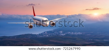 Passenger airplane. Landscape with white airplane is flying in the orange sky with clouds over mountains, sea at colorful sunset. Passenger aircraft is landing. Commercial plane. Private jet. Travel #721267990