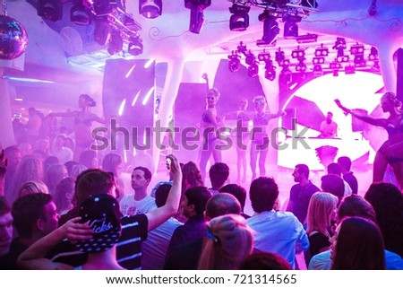 Odessa, Ukraine June 6, 2015: Ibiza club. Night club dj party people enjoy of music dancing sound with colorful light with Smoke Machine and lights show. Hands up in the earth. #721314565